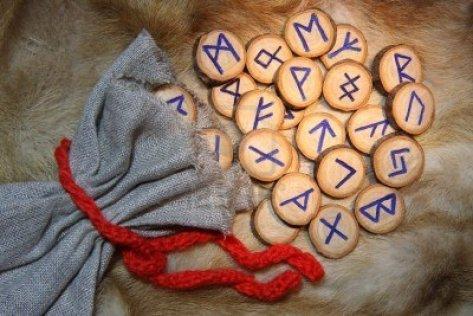 2443016-a-mano-de-madera-con-runas-bolsa
